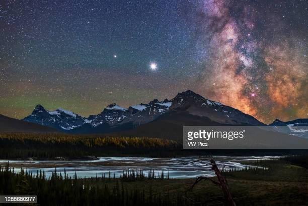 Jupiter , Saturn , and the Milky Way over the Saskatchewan River and the area of Howse Pass, on July 26, 2020. Mount Cephren is at left; the scene is...