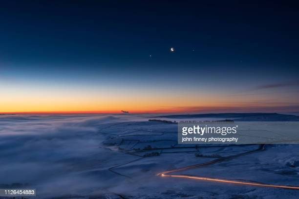 jupiter, venus, moon conjunction over freezing fog and snow. peak district. uk - atmospheric mood stock pictures, royalty-free photos & images