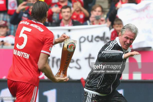 Jupp Henyckes head coach of FC Bayern Muenchen is drenched in beer by his palyer Daniel van Buyten following their match against Augsburg at the...