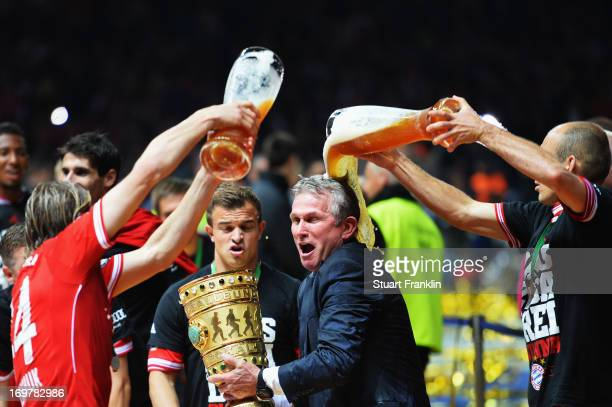 Jupp Heynckes head coach of Bayern Muenchen is showered with beer by Anatoliy Tymoshchuk and Arjen Robben as he celebrates victory in his last match...