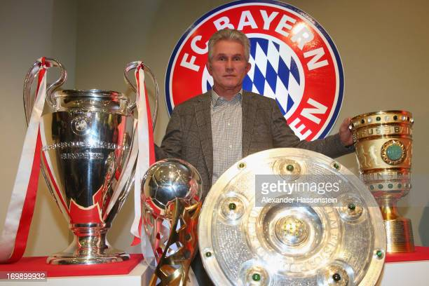 Jupp Heynckes of FC Bayern Muenchen poses with the Champions League winners trophy the German Super Cup winners trophy German League winners trophy...