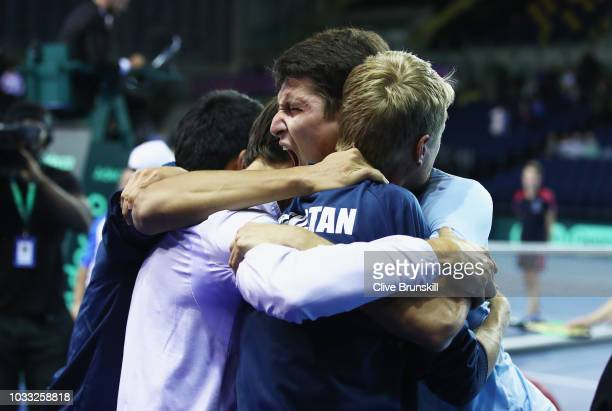 Jurabek Karimov of Uzbekistan celebrates with his team mates after his five set victory against Cameron Norrie of Great Britain during day one of the...