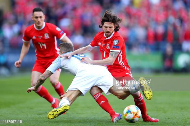 Juraj Kucka of Slovakia is challenged by Joe Allen of Wales during the 2020 UEFA European Championships group E qualifying match between Wales and...