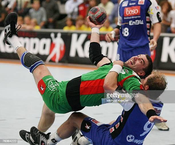 Jurecki Bartosz of SC Magdeburg battles for the ball with Frank Ettwein of BailingenWeilstetten during the Handball Bundesliga match between...