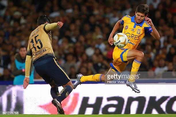 Jurgen Damm of Tigres jumps to control the ball as he is observed by Eduardo Herrera of Pumas during the final second leg match between Pumas UNAM...