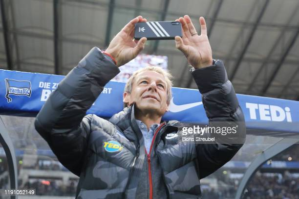 Jurgen Klinsmann Head Coach of Hertha BSC takes a photograph prior to the Bundesliga match between Hertha BSC and Borussia Dortmund at Olympiastadion...