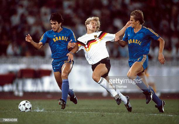 Jurgen Klinsmann of the West Germany team is forced off the ball by Andre Cruz of Brazil during the semifinal match of the Men's football tournament...