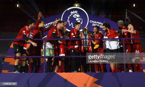 Jurgen Klopp, Adam Lallana and Mohamed Salah of Liverpool hold the Premier League Trophy as they celebrate winning the League Title during the...