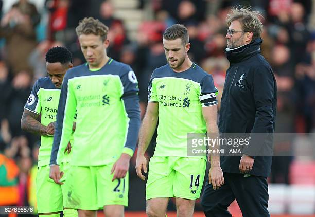 Jurgen Klopp manager / head coach of Liverpool walks behind a dejected looking Jordan Henderson Lucas Leiva and Nathaniel Clyne of Liverpool during...