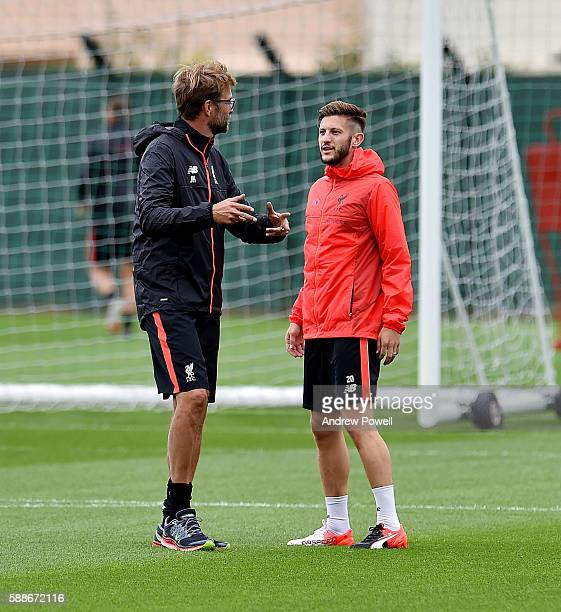 Jurgen Klopp manager of Liverpool and Adam Lallana chat during a training session at Melwood Training Ground on August 12 2016 in Liverpool England