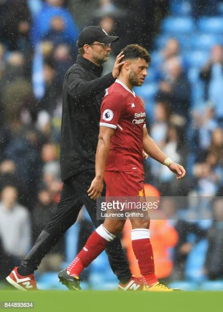 Jurgen Klopp Manager of Liverpool and Alex OxladeChamberlain of Liverpool embrace after the Premier League match between Manchester City and...