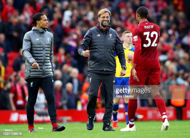 Jurgen Klopp Manager of Liverpool and Joel Matip of Liverpool celebrate following their sides victory in the Premier League match between Liverpool...