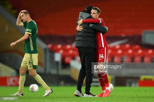 Jurgen Klopp Manager of Liverpool and Jordan Henderson of Liverpool celebrate following their team's victory in the Premier League match between...