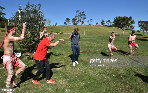 Jurgen Klopp manager of Liverpool and Peter Moore CEO of Liverpool perform with the Muggera dancers during a Aboriginal culture tour on Walumil Lawn...
