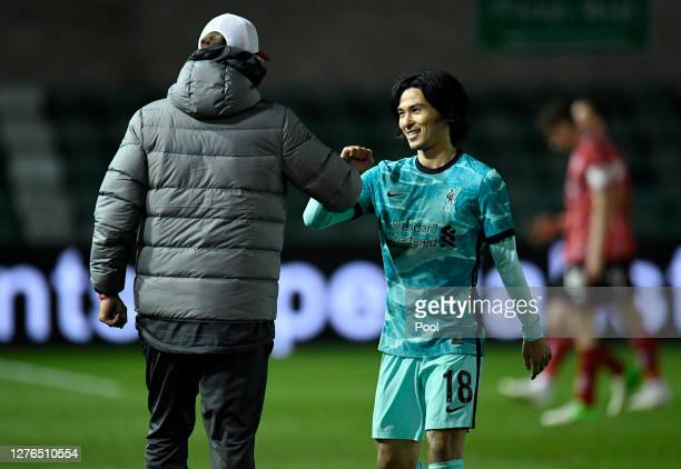 Jurgen Klopp Manager of Liverpool and Takumi Minamino of Liverpool celebrate following their team's victory in the Carabao Cup third round match...