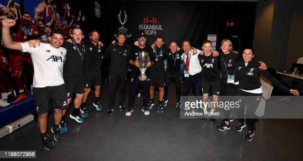 Jurgen Klopp manager of Liverpool and the back room staff with the UEFA Super Cup trophy in the dressing room at the end of the UEFA Super Cup match...
