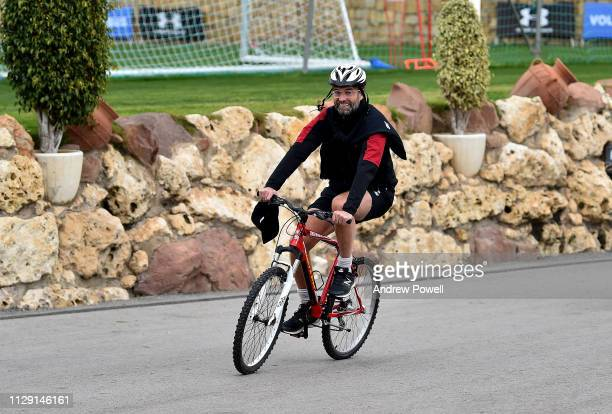 Jurgen Klopp manager of Liverpool arrives before a training session riding a bike on February 12, 2019 in Marbella, Spain.