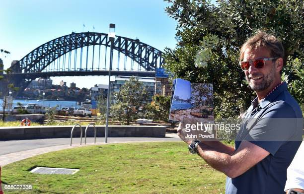 Jurgen Klopp manager of Liverpool checks the view in a book he has been given is the same as the one he is standing in front of during a Aboriginal...
