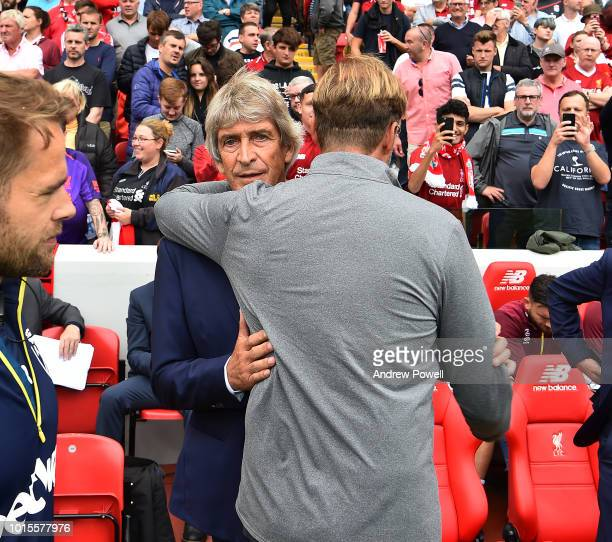 Jurgen Klopp manager of Liverpool embracing Manuel Pellegrini manager of West Ham United before the Premier League match between Liverpool FC and...