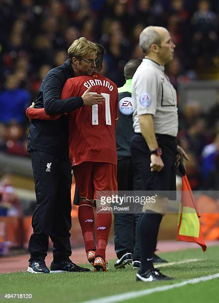 Jurgen Klopp manager of Liverpool gives Roberto Firmino of Liverpool a hug during the Capital One Cup Fourth Round match between Liverpool and AFC...