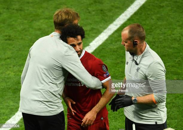 Jurgen Klopp Manager of Liverpool greets Mohamed Salah of Liverpool as he leaves the pitch injured during the UEFA Champions League Final between...
