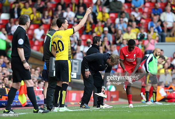 Jurgen Klopp manager of Liverpool helps Sheyi Ojo with his boots during the Barclays Premier League match between Liverpool and Watford at Anfield on...