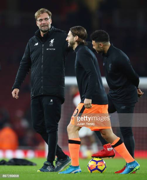 Jurgen Klopp Manager of Liverpool in discussion with Alex OxladeChamberlain and Adam Lallana of Liverpool prior to the Premier League match between...