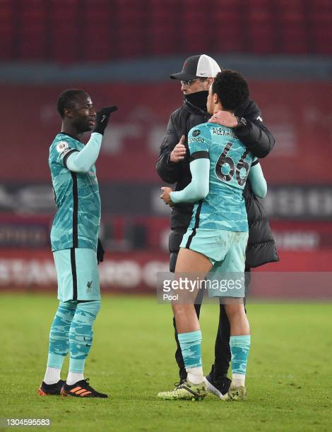 Jurgen Klopp, Manager of Liverpool interacts with Trent Alexander-Arnold and Naby Keita of Liverpool during the Premier League match between...