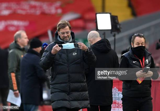 Jurgen Klopp, Manager of Liverpool is seen holding a face mask as he prepares to speak to the media ahead of the Premier League match between...