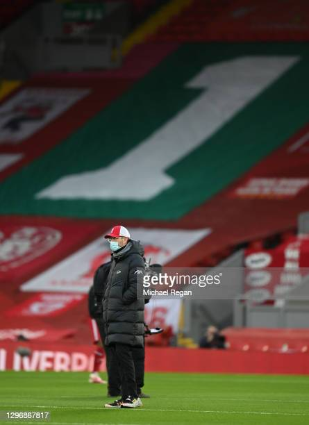 Jurgen Klopp, Manager of Liverpool is seen wearing a face mask as he inspects the pitch ahead of the Premier League match between Liverpool and...