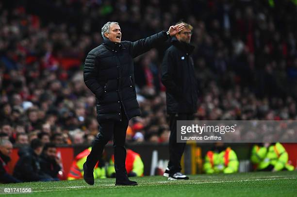 Jurgen Klopp manager of Liverpool looks on as Jose Mourinho manager of Manchester United gives instructions during the Premier League match between...