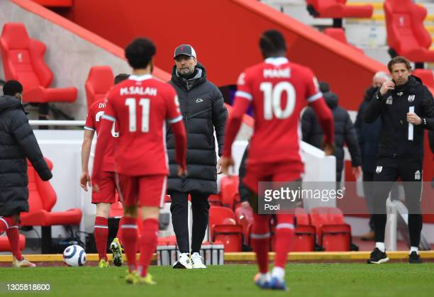 Jurgen Klopp, Manager of Liverpool looks on as Mohamed Salah and Sadio Mane of Liverpool leave the pitch following the Premier League match between...