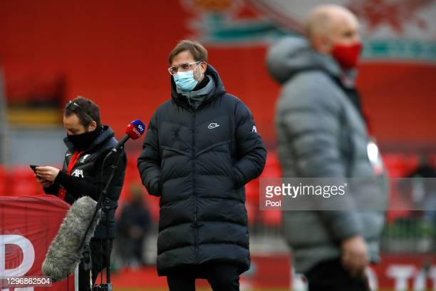 Jurgen Klopp, Manager of Liverpool looks on whilst wearing a protective face mask as he is interviewed ahead of the Premier League match between...