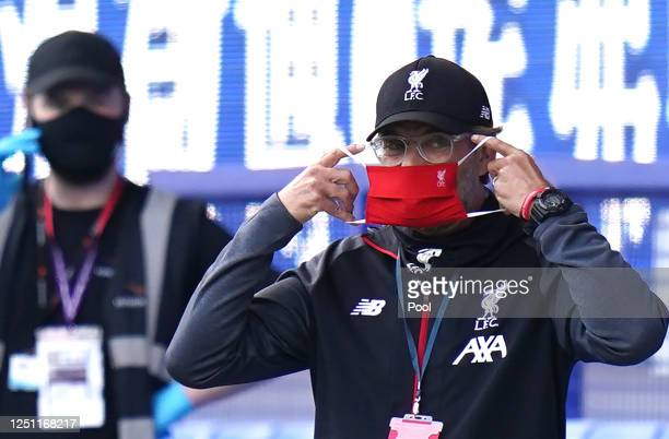 Jurgen Klopp, Manager of Liverpool puts on his face mask during the Premier League match between Everton FC and Liverpool FC at Goodison Park on June...
