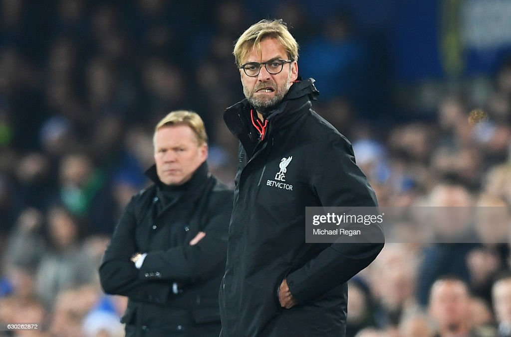 Jurgen Klopp manager of Liverpool reacts as Ronald Koeman manager of Everton looks on during the Premier League match between Everton and Liverpool at Goodison Park on December 19, 2016 in Liverpool, England.
