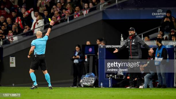 Jurgen Klopp manager of Liverpool receiving a yellow card from referee Szymon Marciniak during the UEFA Champions League round of 16 first leg match...