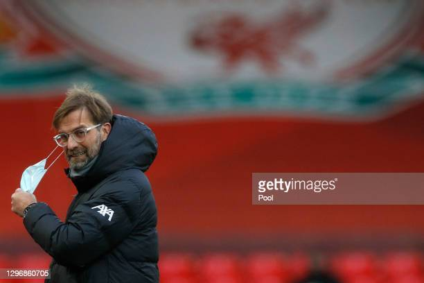 Jurgen Klopp, Manager of Liverpool removes his face mask ahead of being interviewed prior to kick off during the Premier League match between...