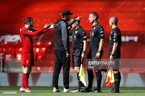 Jurgen Klopp Manager of Liverpool speaks with Match Referee David Coote following the Premier League match between Liverpool FC and Burnley FC at...