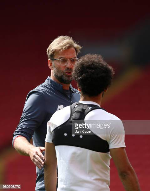 Jurgen Klopp Manager of Liverpool speaks with Mohamed Salah during a training session at Anfield on May 21 2018 in Liverpool England