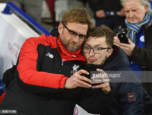 Jurgen Klopp manager of Liverpool takes a selfie with a Leicester City fan during the Barclays Premier League match between Leicester City and...