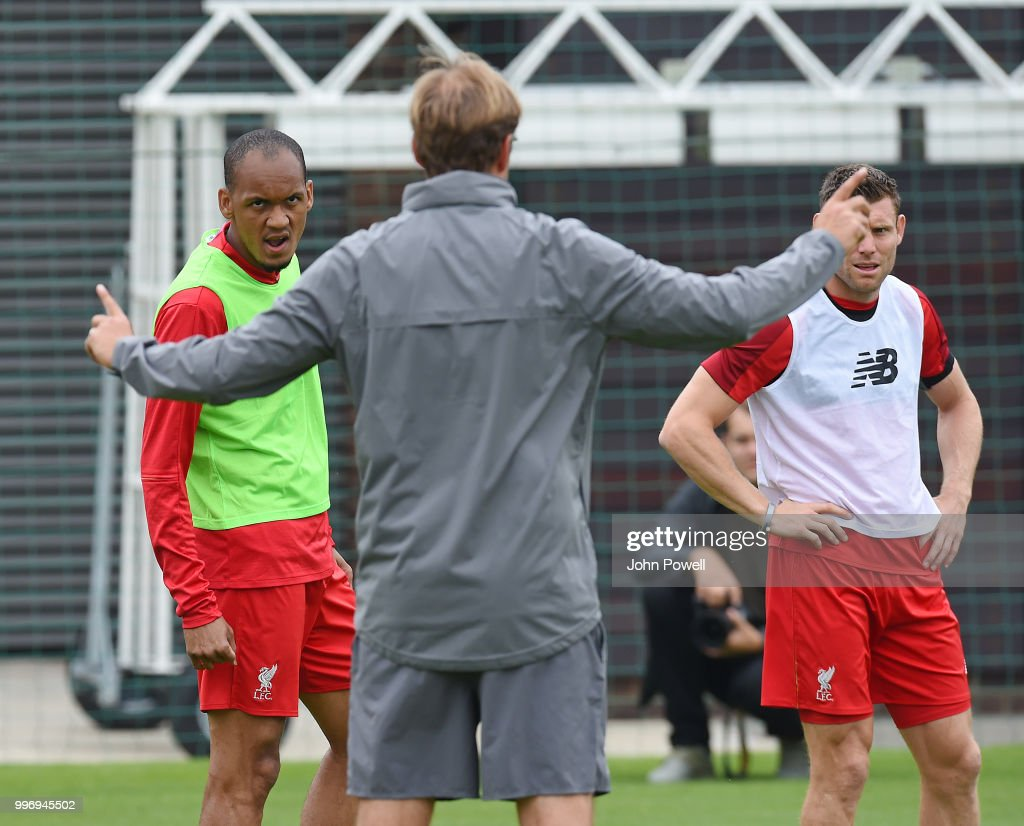 Jurgen Klopp manager of Liverpool talking with Fabinho and James Milner during a training session at Melwood Training Ground on July 12, 2018 in Liverpool, England.