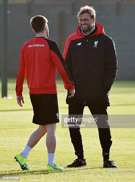 Jurgen Klopp manager of Liverpool talks with Adam Lallana during a training session at Melwood Training Ground on January 22 2016 in Liverpool England