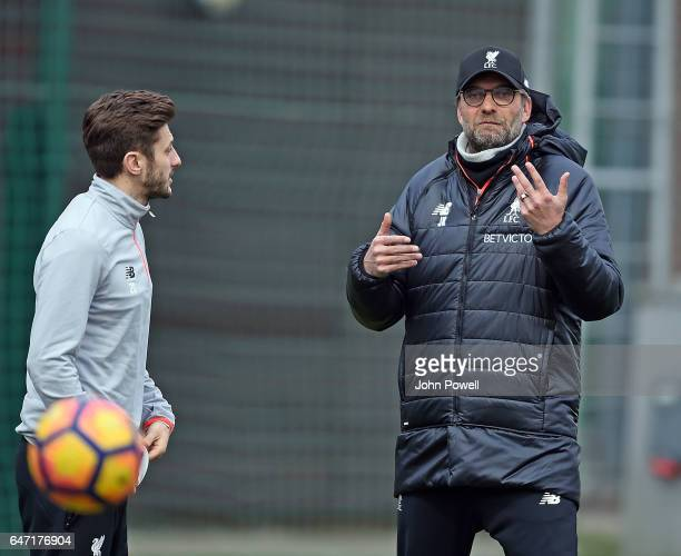 Jurgen Klopp manager of Liverpool talks with Adam Lallana of Liverpool during a training session at Melwood Training Ground on March 2 2017 in...