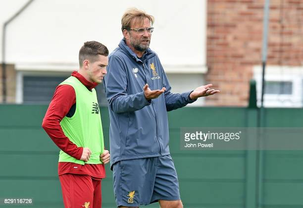 Jurgen Klopp manager of Liverpool talks with Ryan Kent 0f Liverpoolduring a training session at Melwood Training Ground on August 10 2017 in...