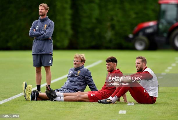 Jurgen Klopp manager of Liverpool with Alex Oxlade Chamberlain and Jordan Henderson during a training session at Melwood Training Ground on September...