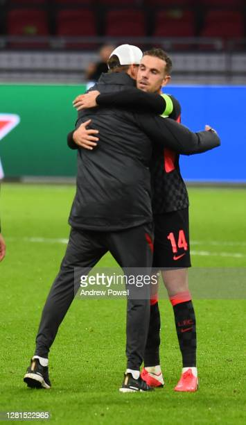 Jurgen Klopp manager of Liverpool with Jordan Henderson captain of Liverpool at the end of the UEFA Champions League Group D stage match between Ajax...