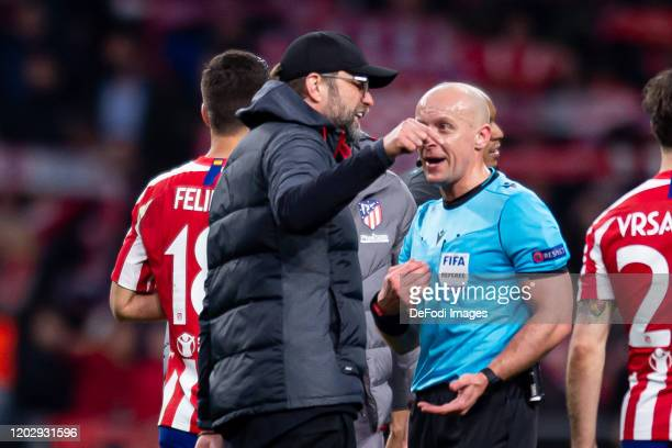 Jurgen Klopp of FC Liverpool speaks with referee Szymon Marciniak during the UEFA Champions League round of 16 first leg match between Atletico...
