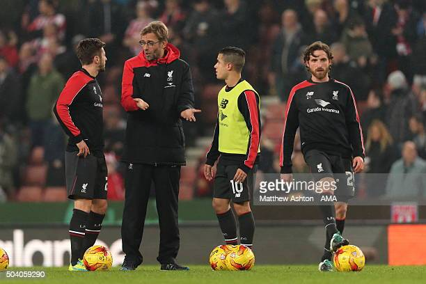 Jurgen Klopp the head coach / manager of Liverpool talks to Adam Lallana and Philippe Coutinho during the Capital One Cup Semi Final First Leg...