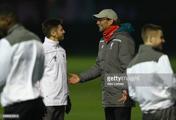 Jurgen Klopp the manager of Liverpool talks with Adam Lallana during a training session at Melwood Training Complex on November 25 2015 in Liverpool...
