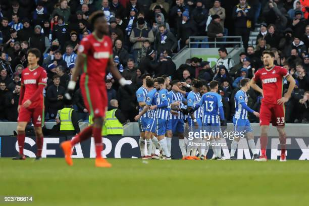 Jurgen Locadia of Brighton is mobbed by team mates celebrating his goal while Swansea players stand in disappointment during the Premier League match...